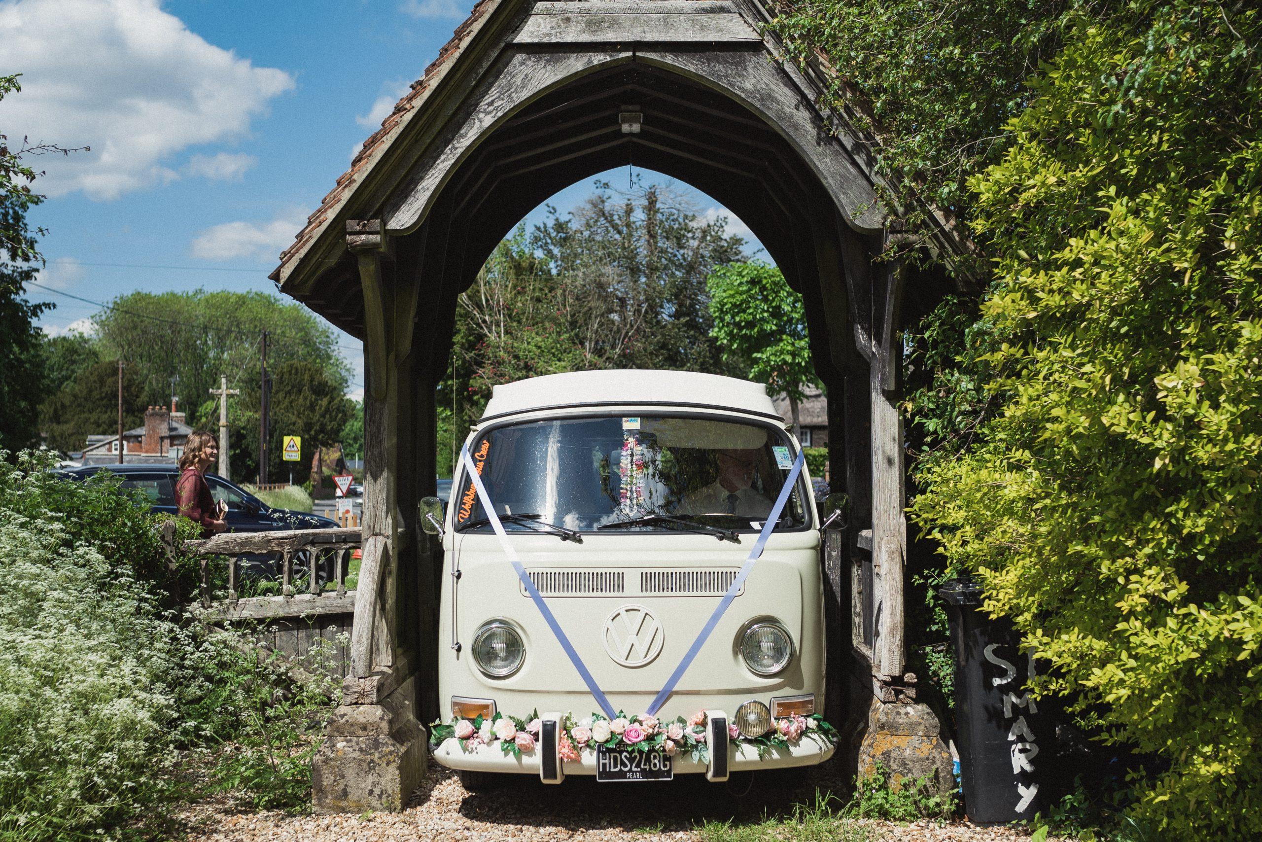 Cream camper van driving through church lychgate