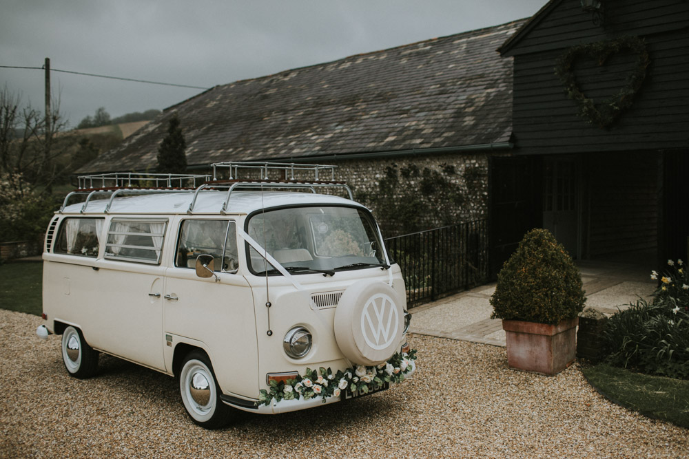 Cream baywindow camper van decorated with flowers and ribbons at Upwaltham Barns